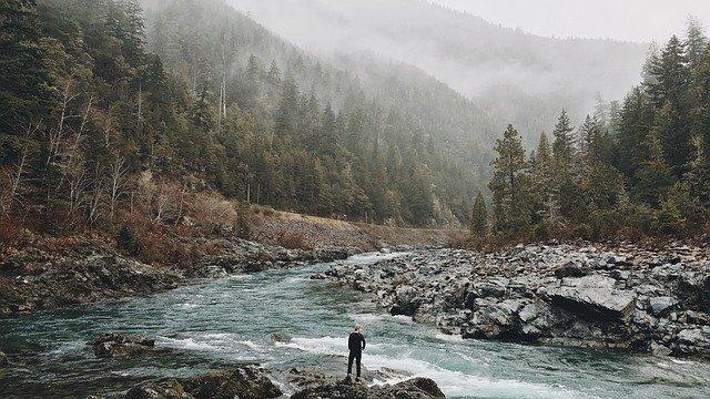 hombre frente a un arroyo
